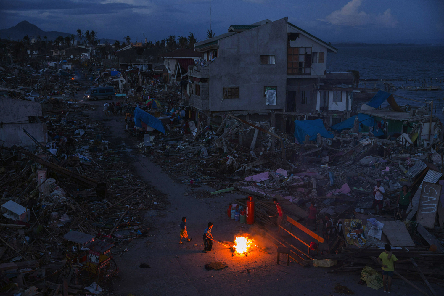 People play by a fire in a neighborhood destroyed by Typhoon Haiyan in Tacloban, Philippines on November 16, 2013.