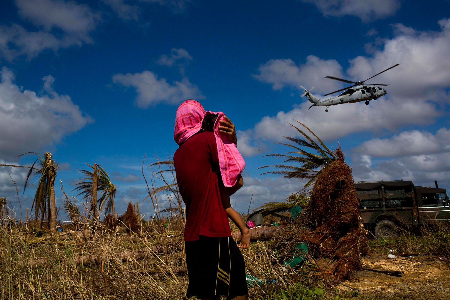 A Typhoon Haiyan survivor carries a child wrapped in a towel as he watches a helicopter landing to bring aid to the destroyed town of Guiuan, Samar Island, Philippines, November 15, 2013.