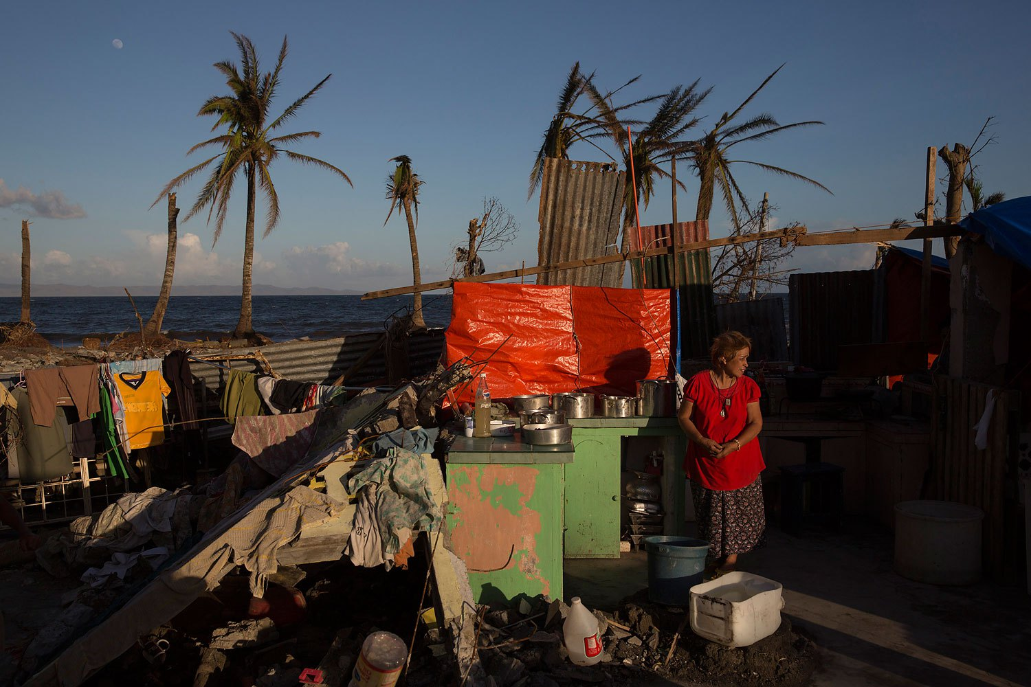 A woman stands in the kitchen of her home destroyed by Typhoon Haiyan in Tanuan,  Philippines on November 15, 2013.