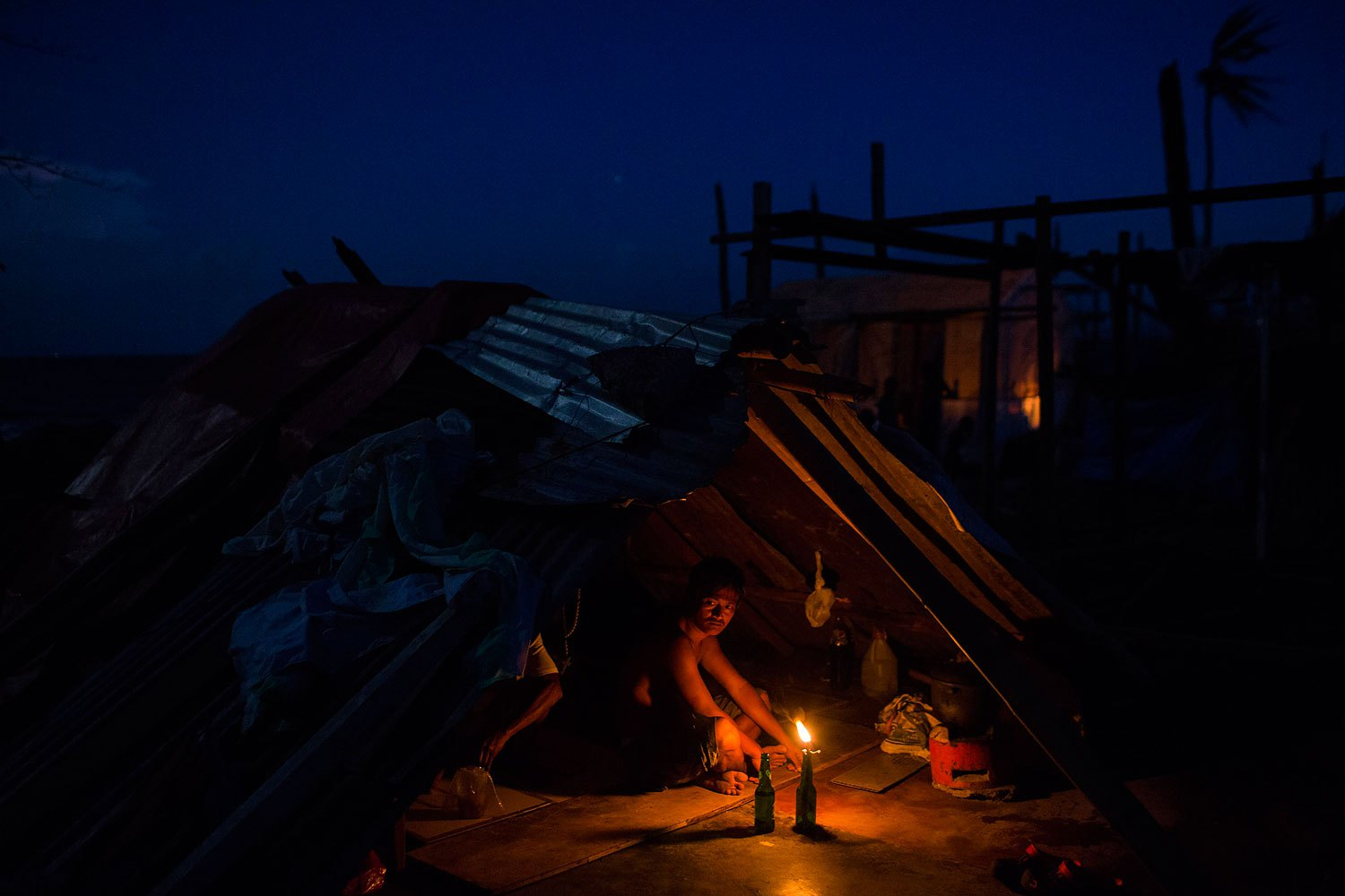 A man who's home was destroyed by Typhoon Haiyan sits by a candle light in the rubble of his home in Tanuan, Philippines on November 15, 2013.