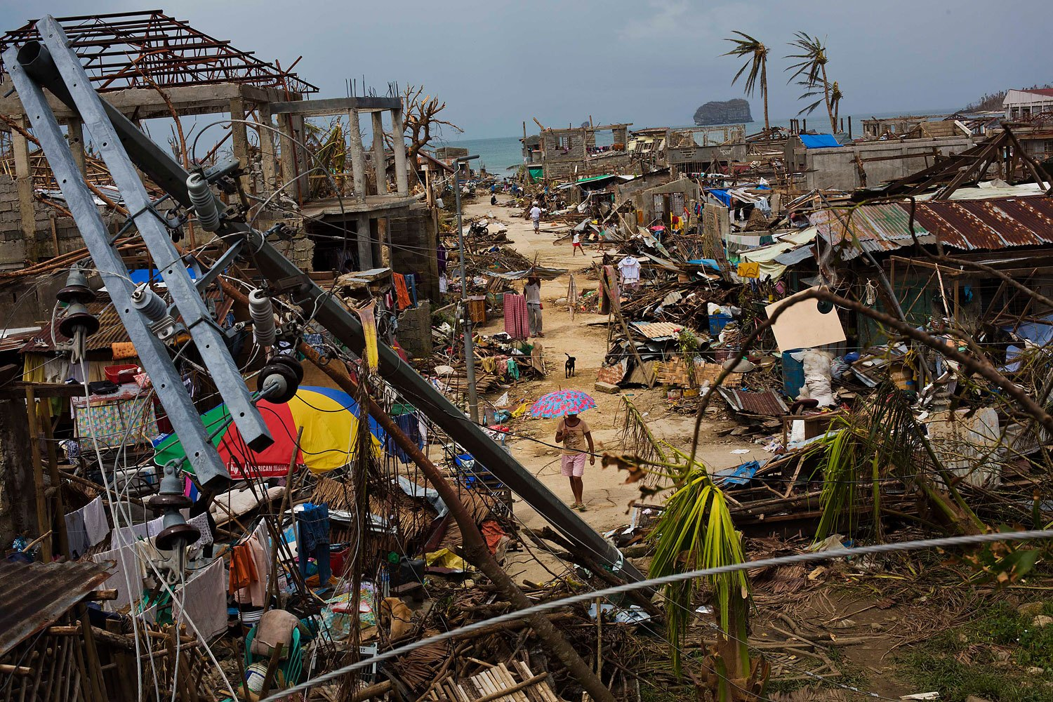 Typhoon Haiyan survivors walk through ruins in the village of Maraboth, in the Philippines on November 14, 2013.