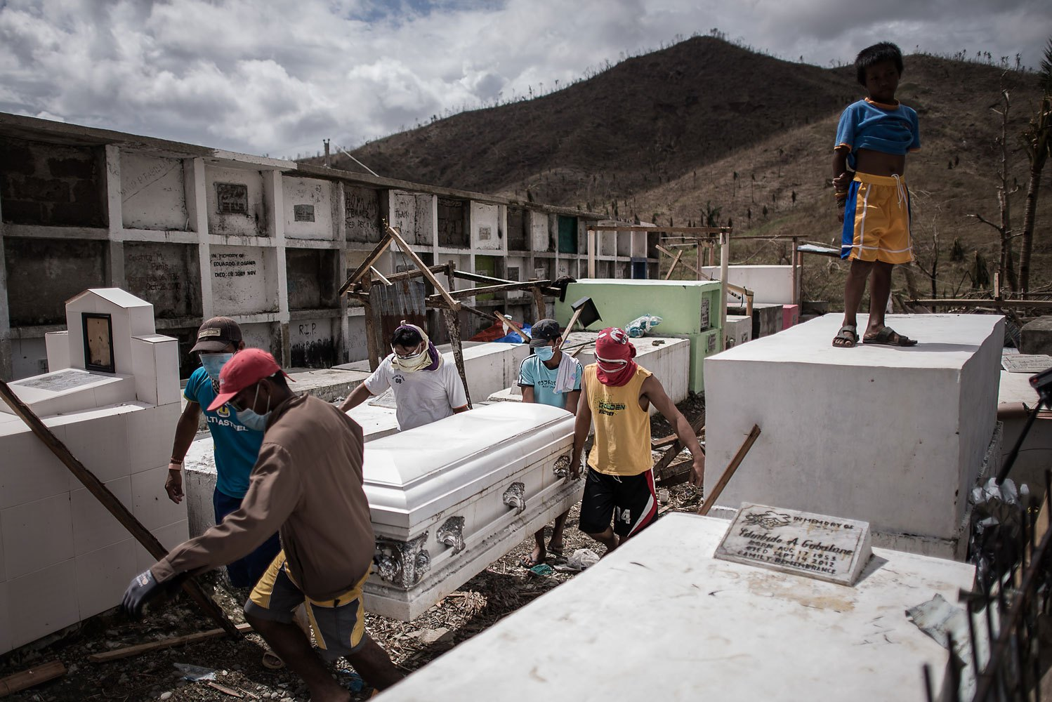 People carry the coffin of a victim of Typhoon Haiyan into a cemetery near a mass grave site, on the outskirts of Tacloban, on the eastern island of Leyte on November 14, 2013.