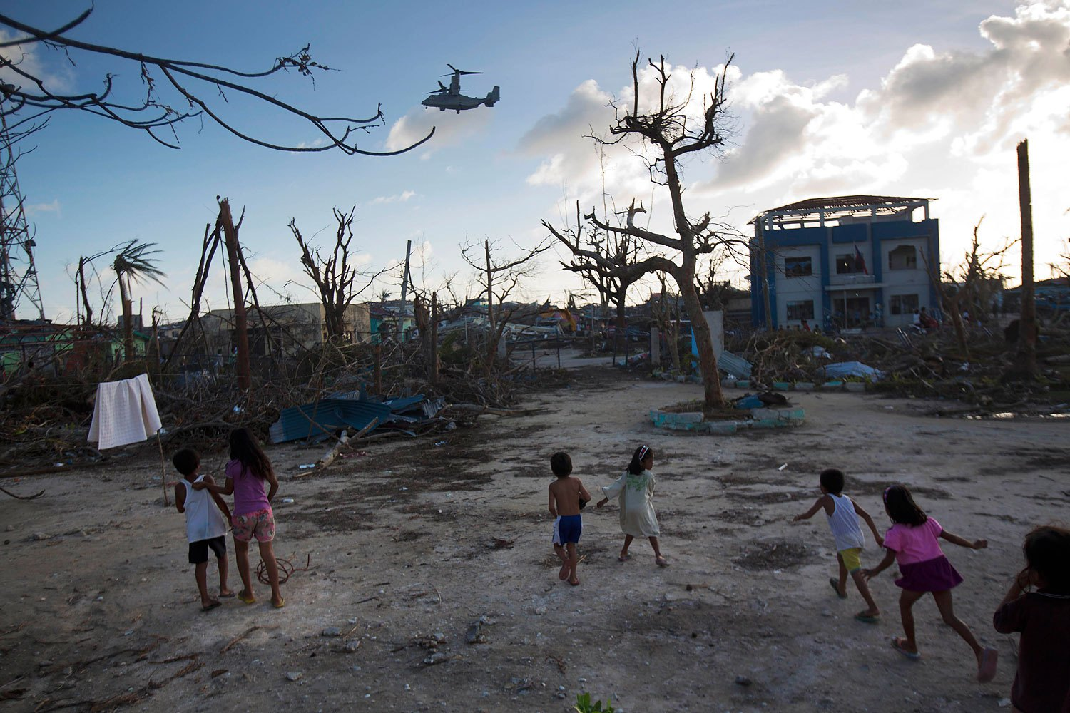 Children run towards a U.S. military aircraft as it arrives to distribute aid to Typhoon Haiyan survivors in the destroyed town of Guiuan, Philippines on November 14, 2013.