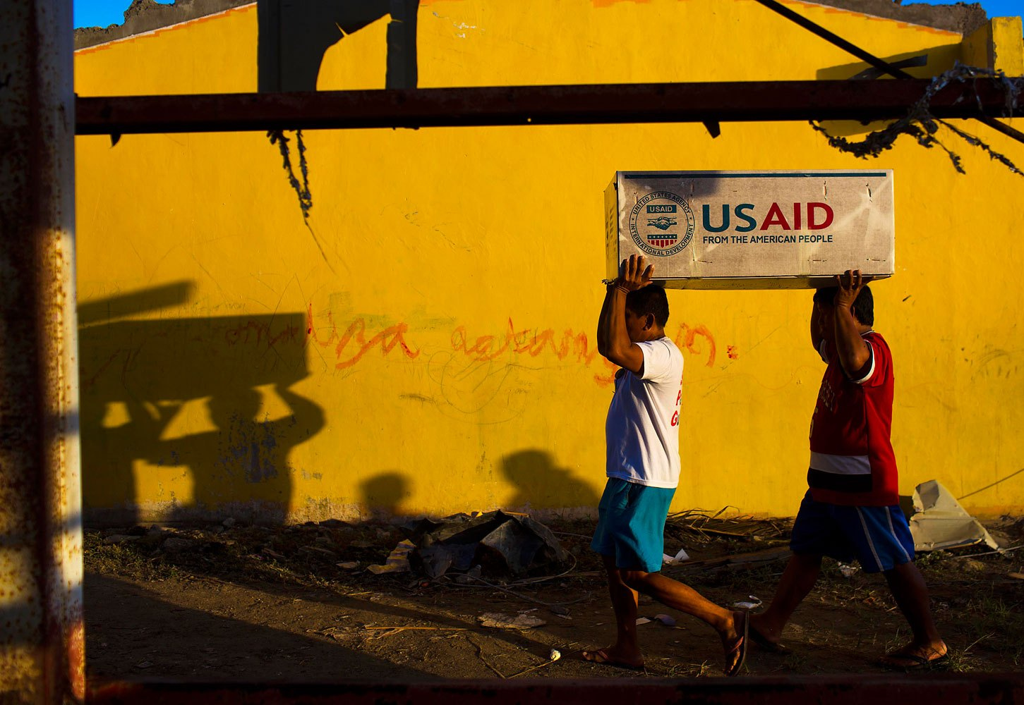Typhoon Haiyan survivors help carry USAID donated food after a U.S. military helicopter unloaded it in the destroyed town of Guiuan, Philippines on November 14, 2013.
