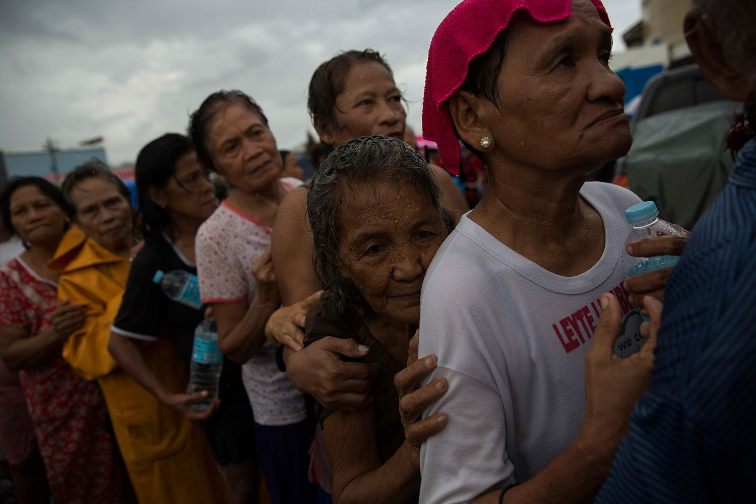 Displaced people effected by Haiyan Typhoon queue in the rain for the first aid delivery at a displacement camp in Tacloban, Philippines on November 14, 2013.
