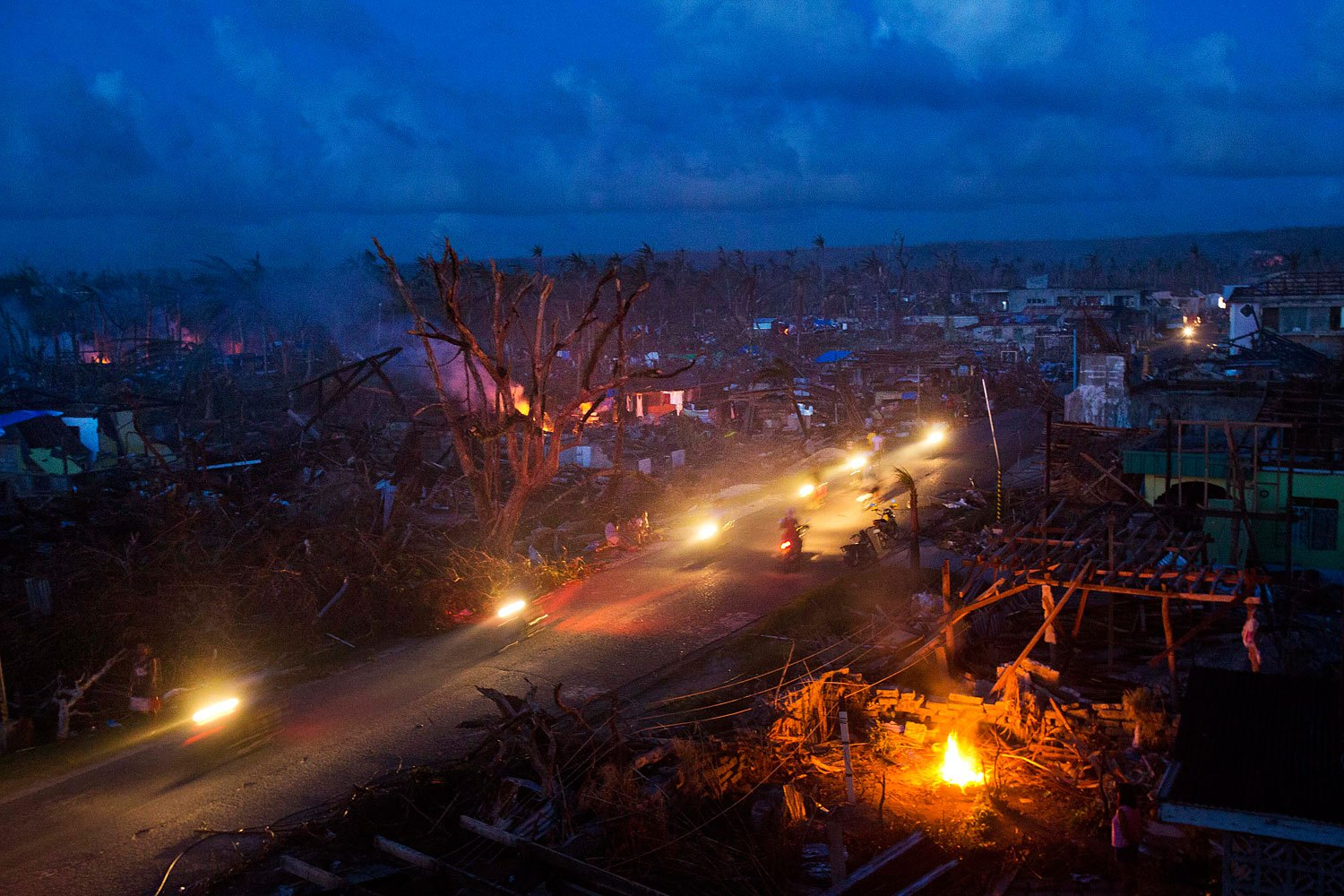 Typhoon Haiyan survivors ride motorbikes through the ruins of the destroyed town of Guiuan, Philippines on November 14, 2013.
