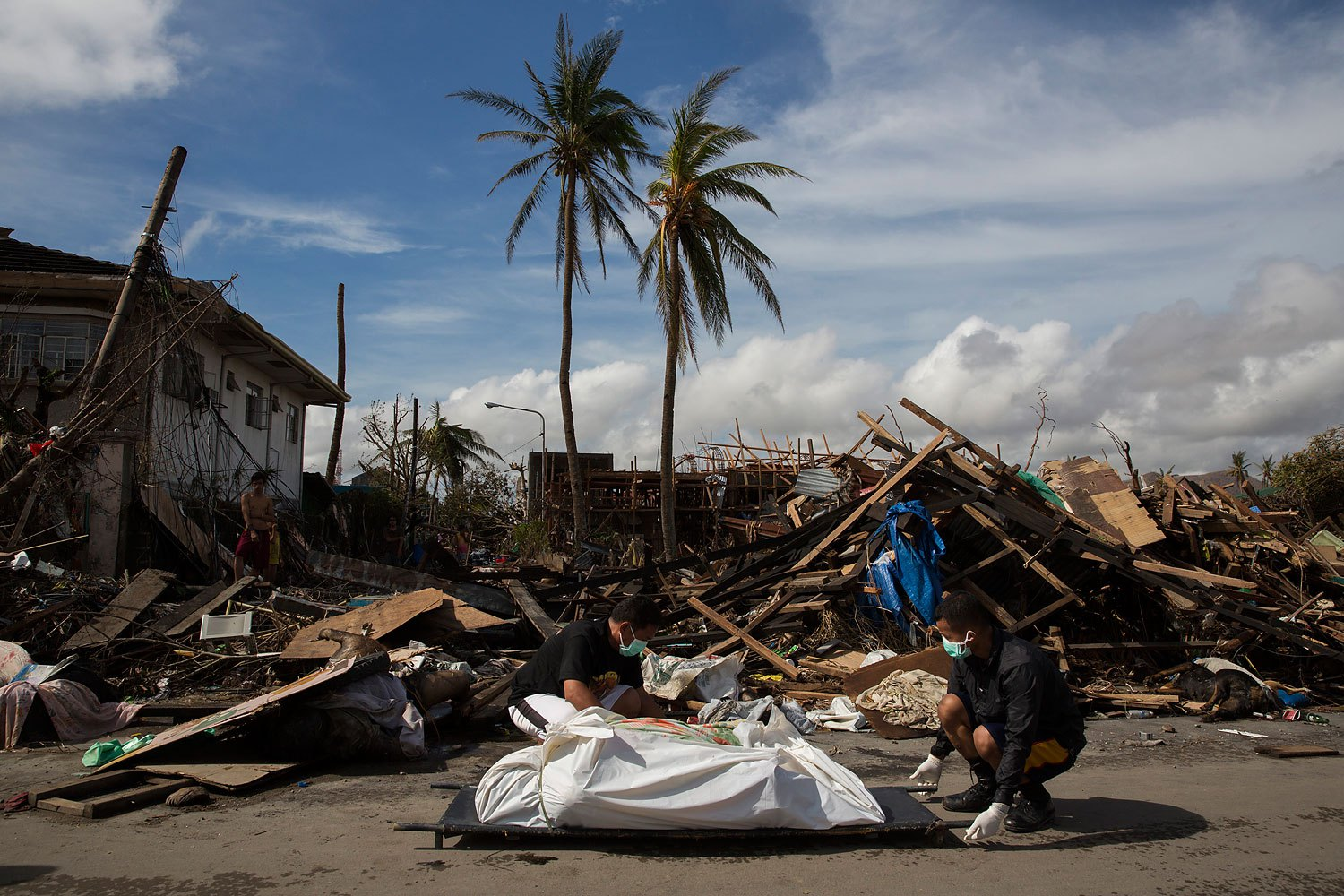 Men remove the body of a woman killed by Haiyan Typhoon in Tacloban, Philippines on November 13, 2013.