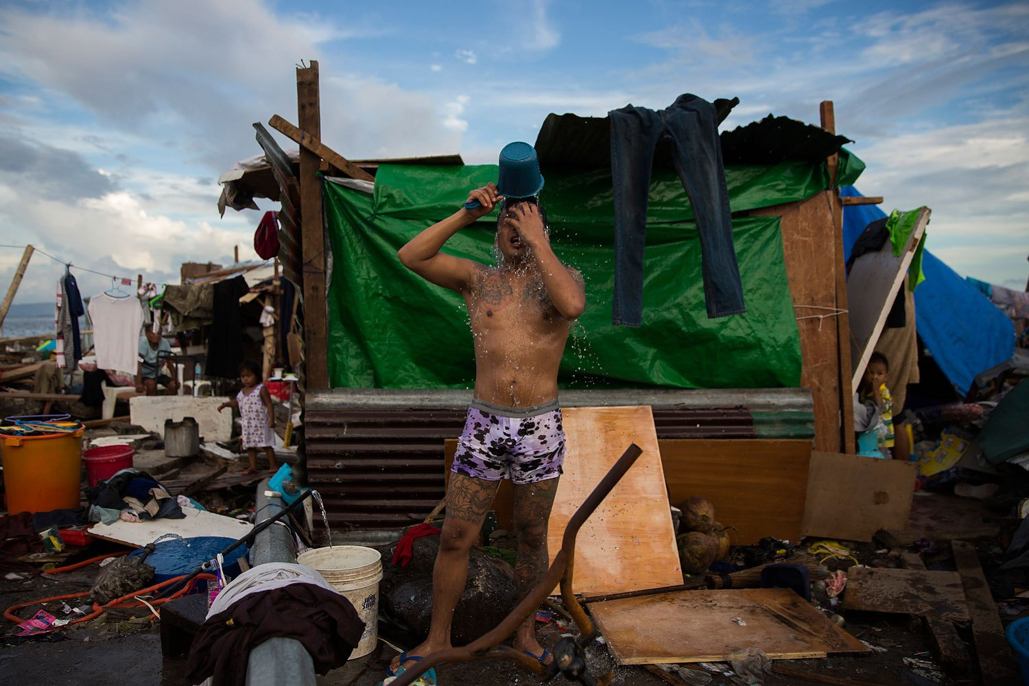 A man washes outside his temporary home on the site of his former home that was destroyed by Haiyan Typhoon in Tacloban, Philippines on November 13, 2013.
