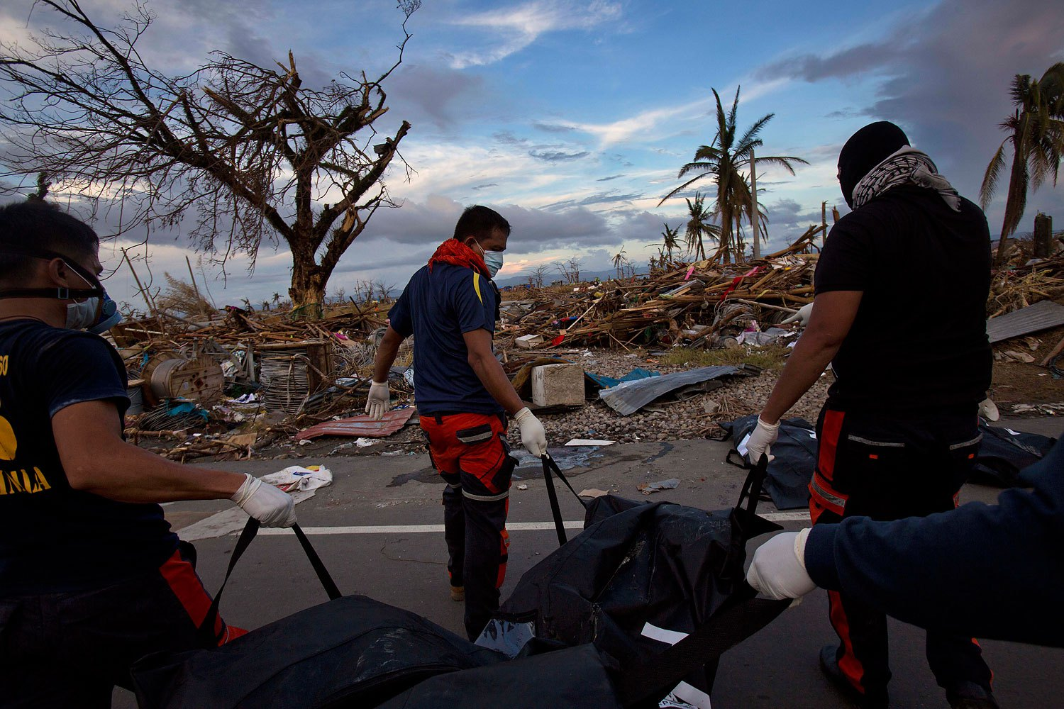 Members of a Philippines rescue team carry corpses in body bags as they search for the dead in the Typhoon Haiyan ravaged city of Tacloban on November 13, 2013.