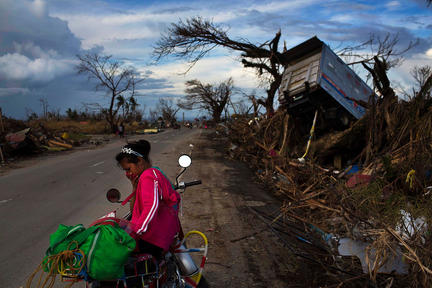 A woman rests on a roadside with her family's belongings near the Typhoon Haiyan ravaged town of Tacloban, Philippines on November 13, 2013.