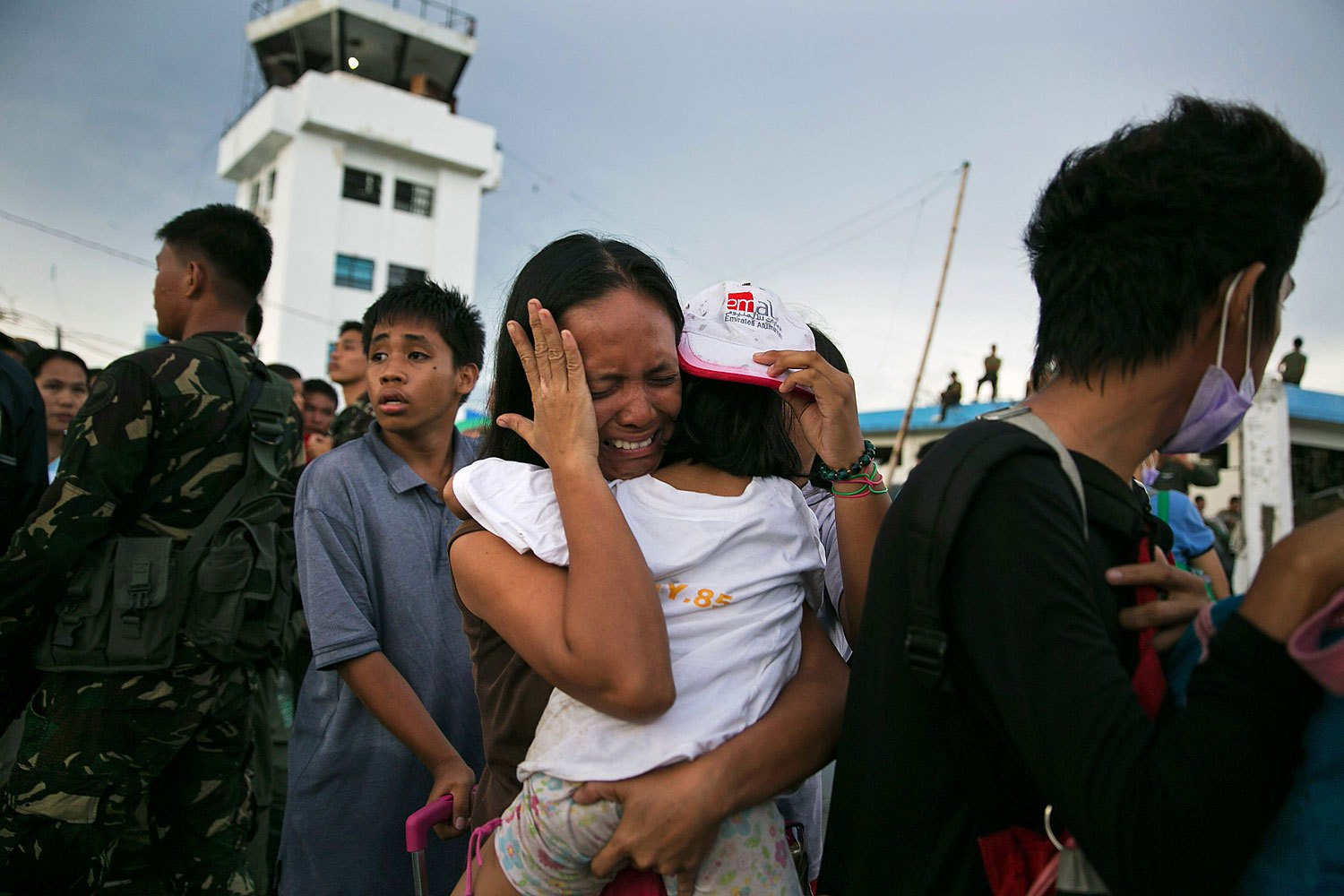 A woman carrying a child cries as they and other survivors of Supertyphoon Haiyan wait to board an aircraft during an evacuation in the Philippine town of Tacloban on Nov. 12, 2013