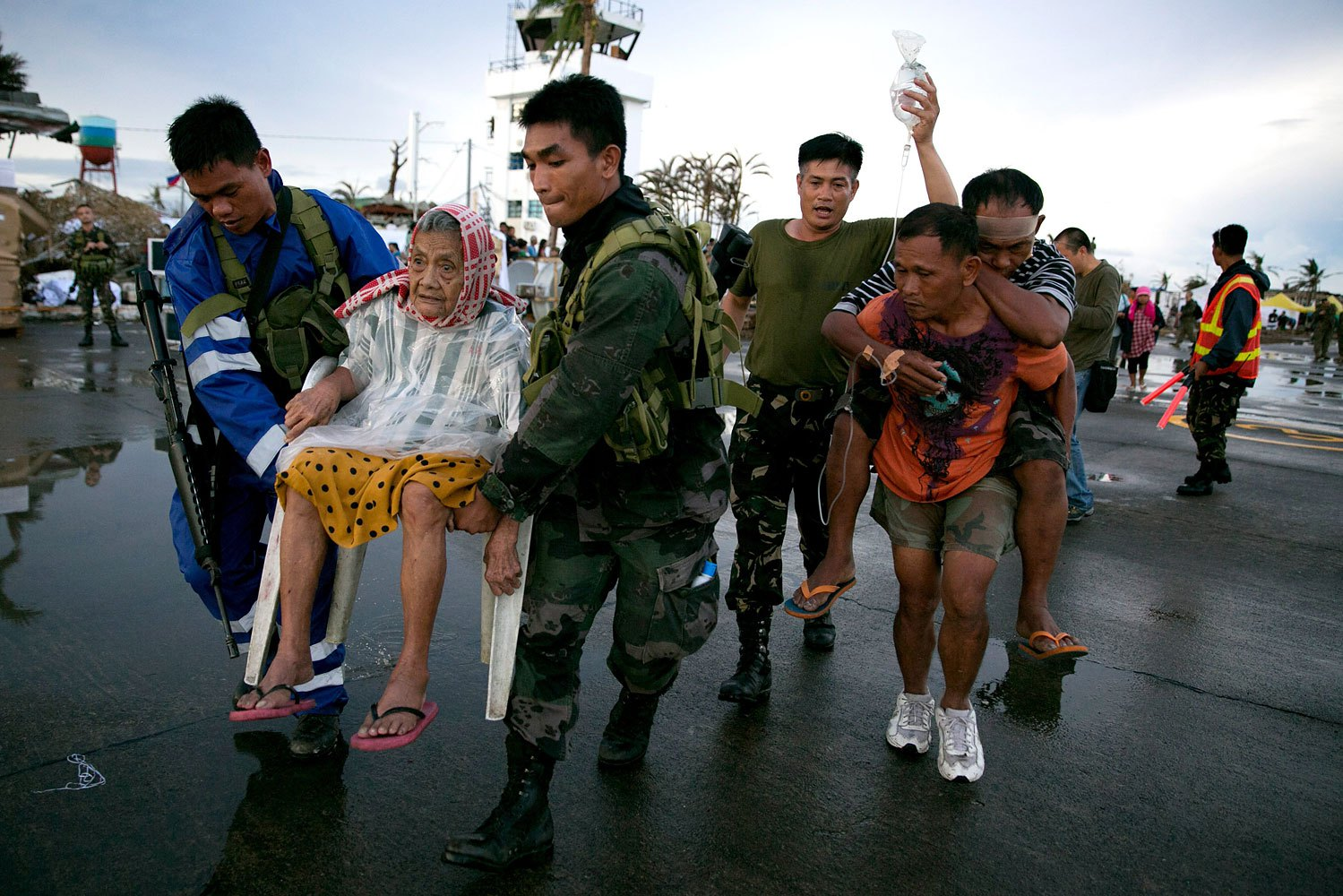 An elderly lady and an injured man are carried to a waiting C130 aircraft during the evacuation of hundreds of survivors of Typhoon Haiyan on November 12, 2013 in Tacloban, Philippines.