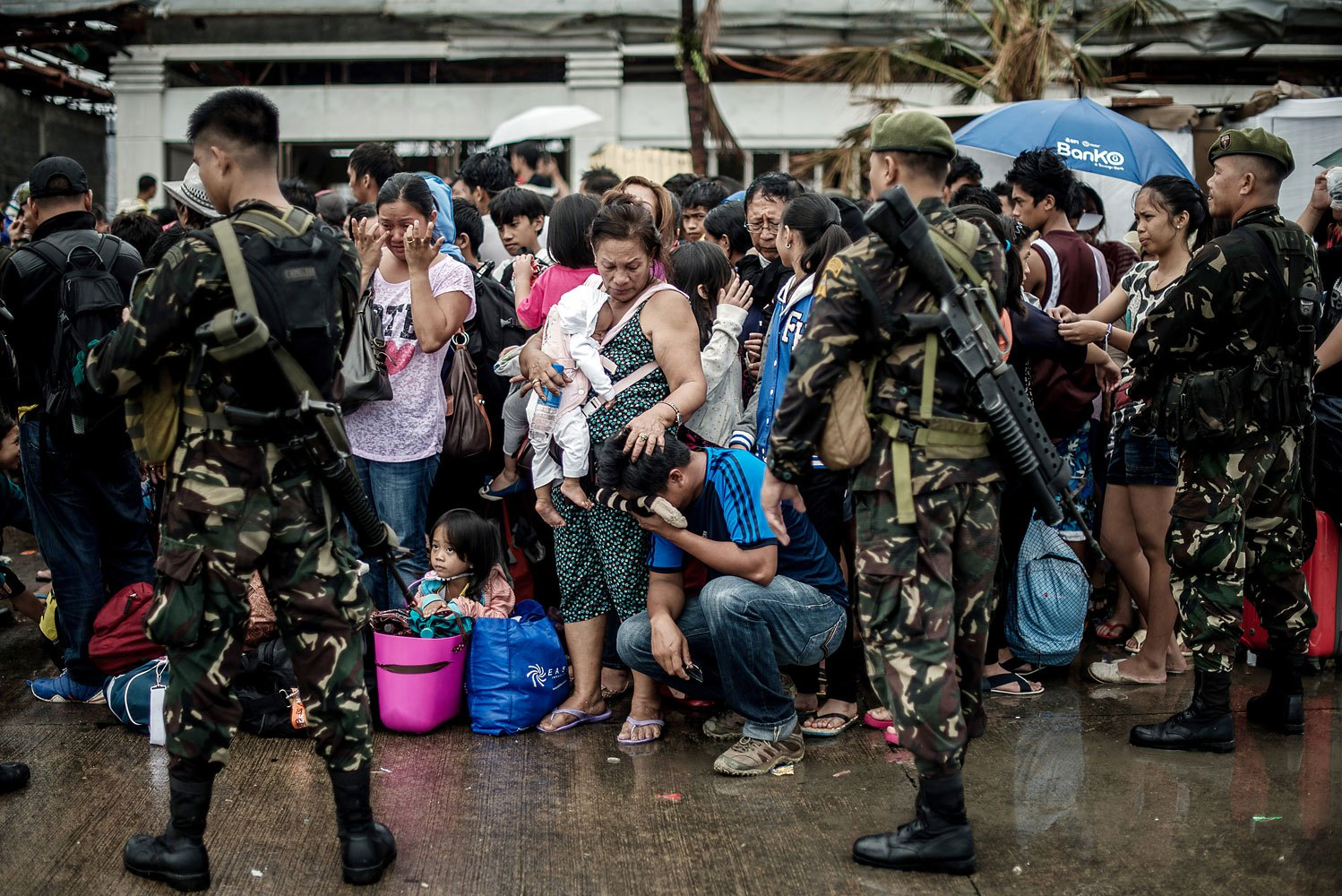 A woman holding a baby comforts a crying relative as a plane leaves the airport during evacuation operations in Tacloban, on the eastern island of Leyte on November 12, 2013 after Super Typhoon Haiyan swept over the Philippines.