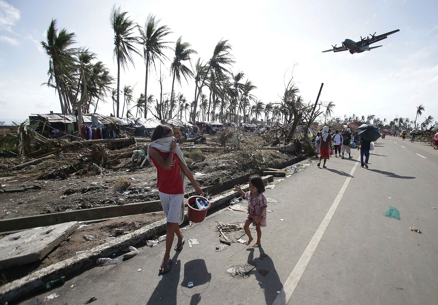 Survivors look up at a military C-130 plane as it arrives at typhoon-ravaged Tacloban city, Leyte province in central Philippines on Nov. 11, 2013.