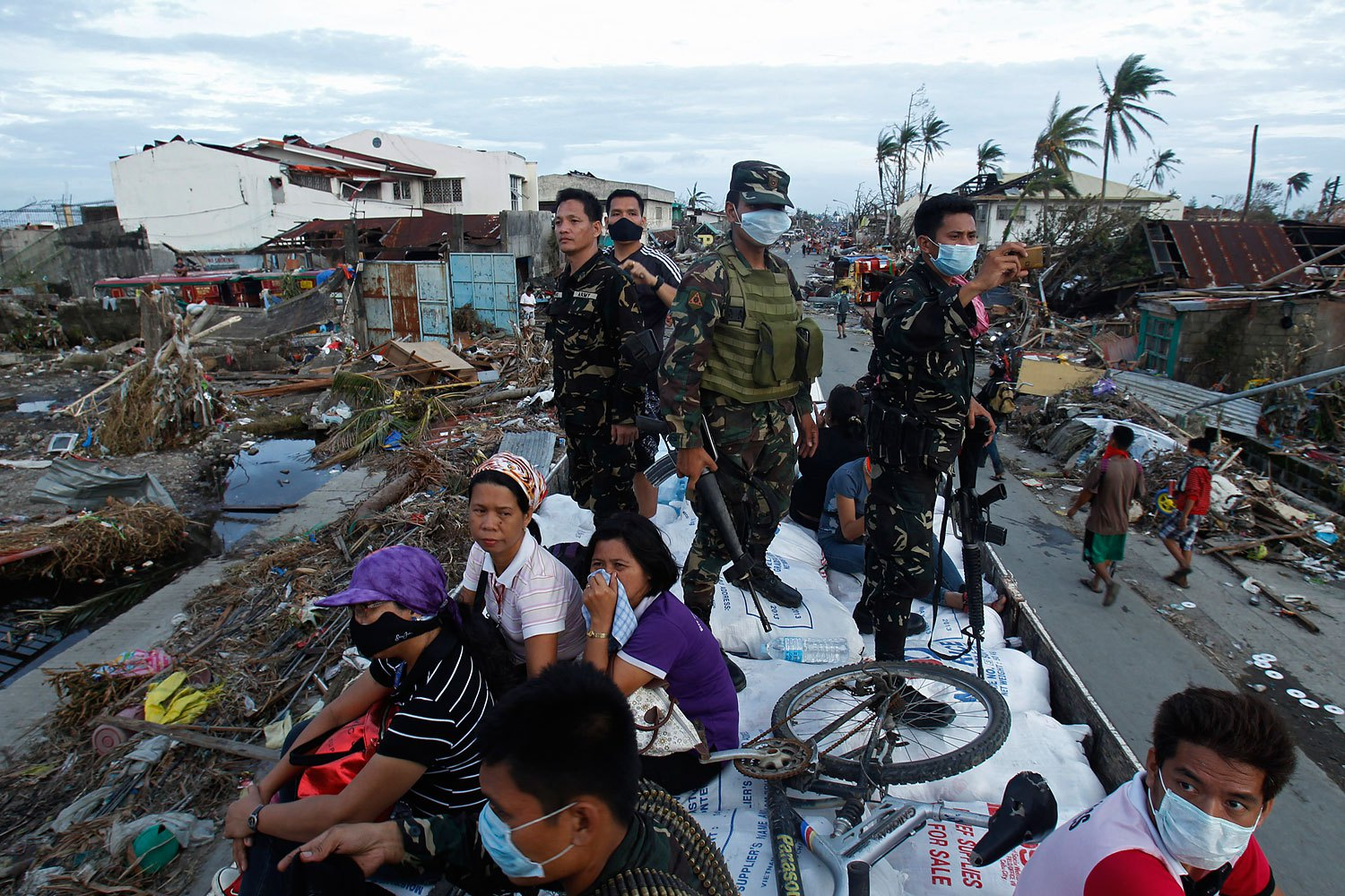 Soldiers and residents look at the devastation of the town from a military aid supplies distribution truck after the Super typhoon Haiyan battered Tacloban city in central Philippines November 11, 2013.