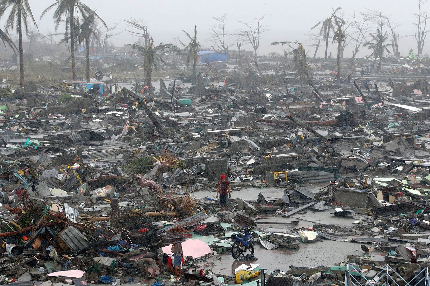 Survivors stand among debris and ruins of houses on Nov. 10, 2013, after Supertyphoon Haiyan battered the city of Tacloban, in central Philippines