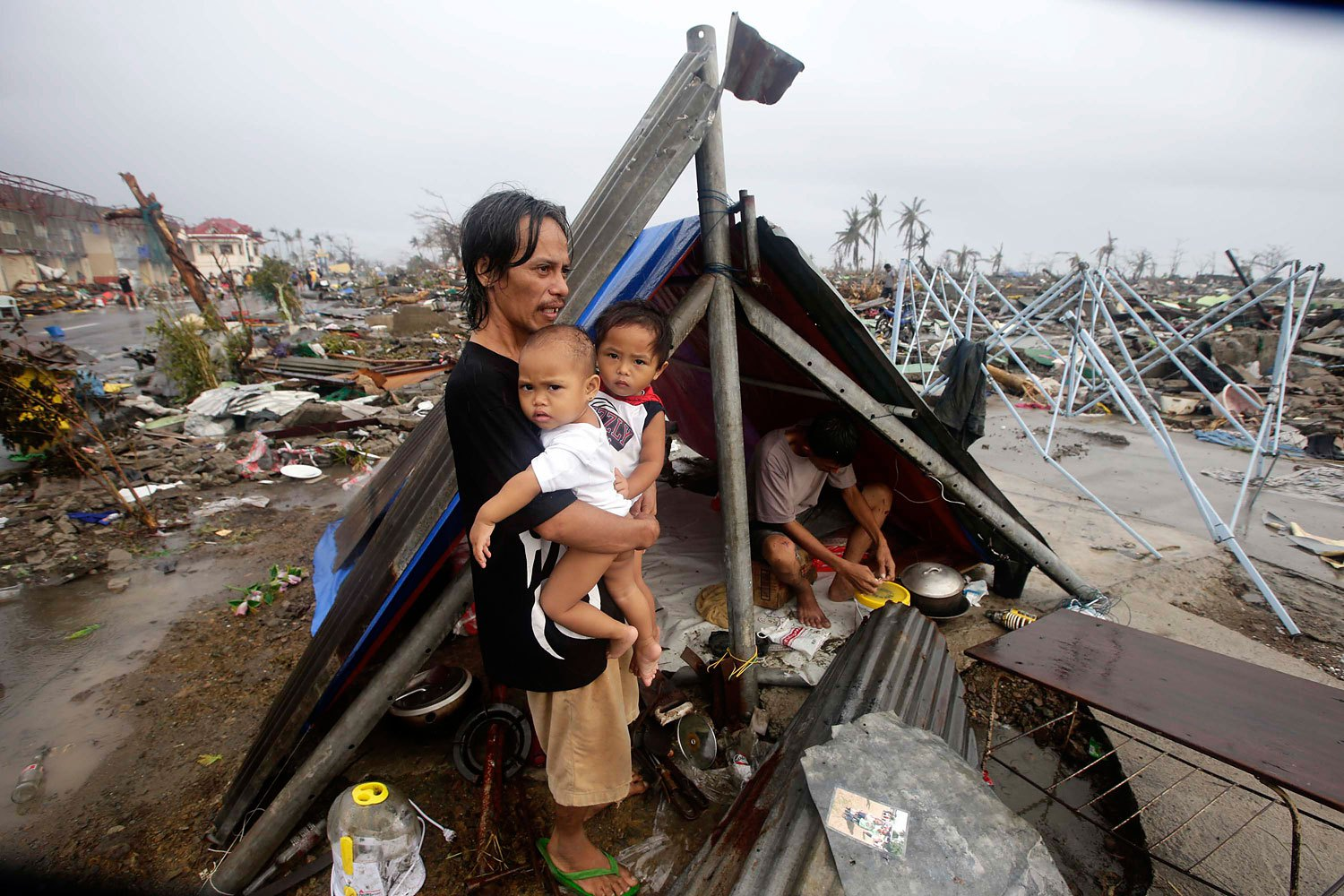A Filipino father and his children wait for food relief outside their makeshift tent in the supertyphoon-devastated city of Tacloban, in the Philippines' Leyte province, on Nov. 10, 2013
