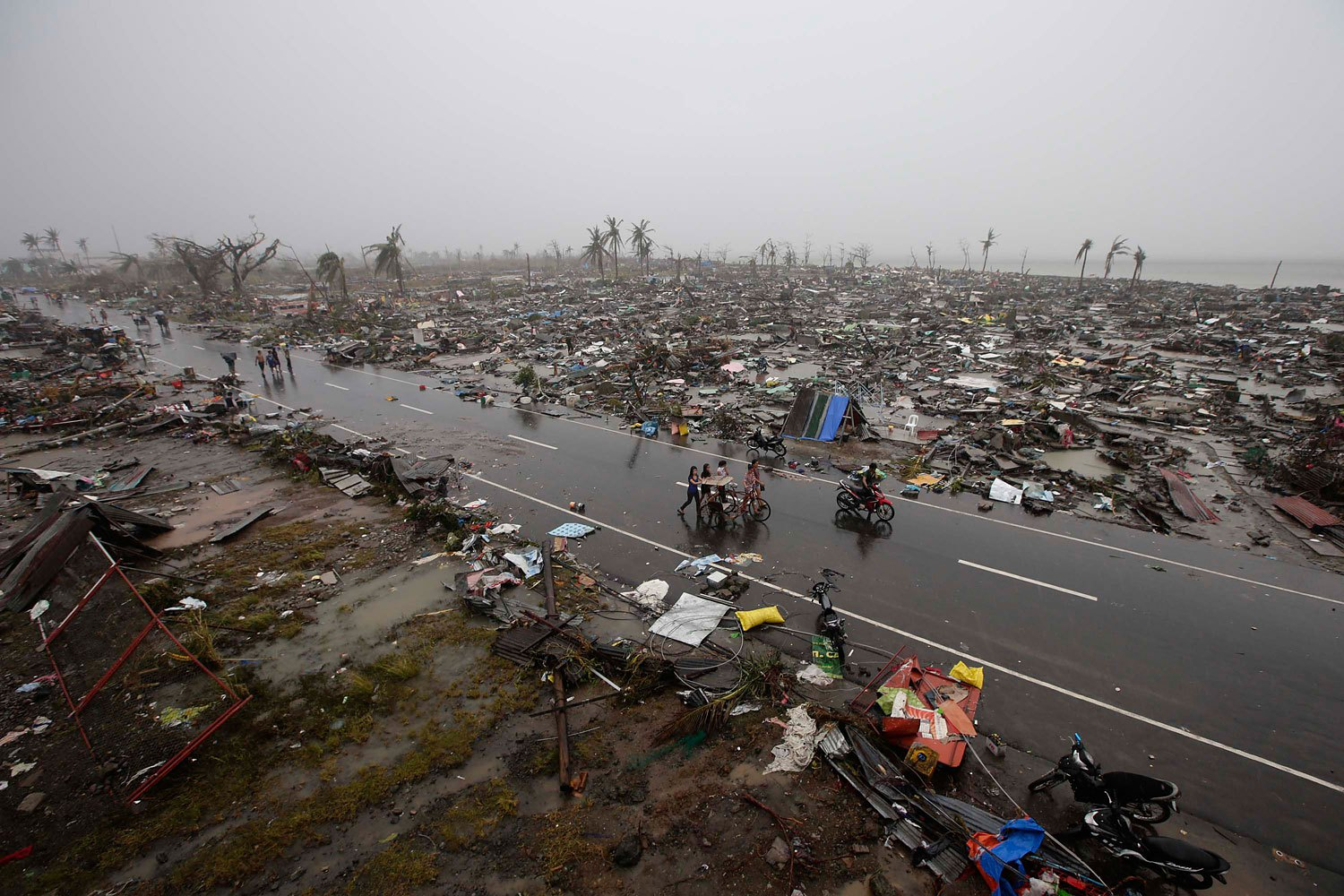 Filipino villagers carrying their belongings during a heavy downpour walk past rubble of houses in the supertyphoon-devastated city of Tacloban, in the Philippines' Leyte province, on Nov. 10, 2013