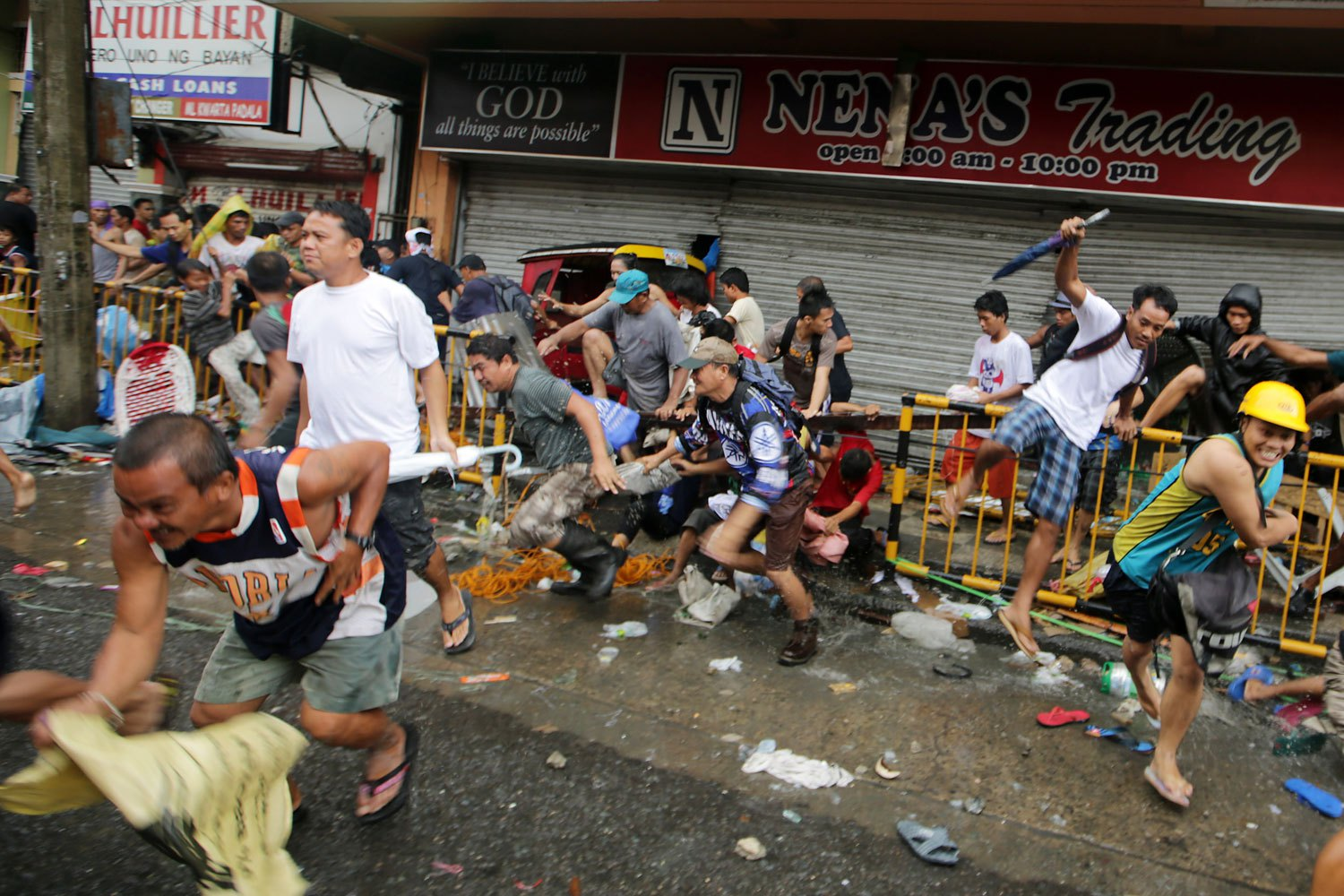 Filipinos rush in front of a store in the super typhoon devastated city of Tacloban, Leyte province, Philippines, November 10,  2013.