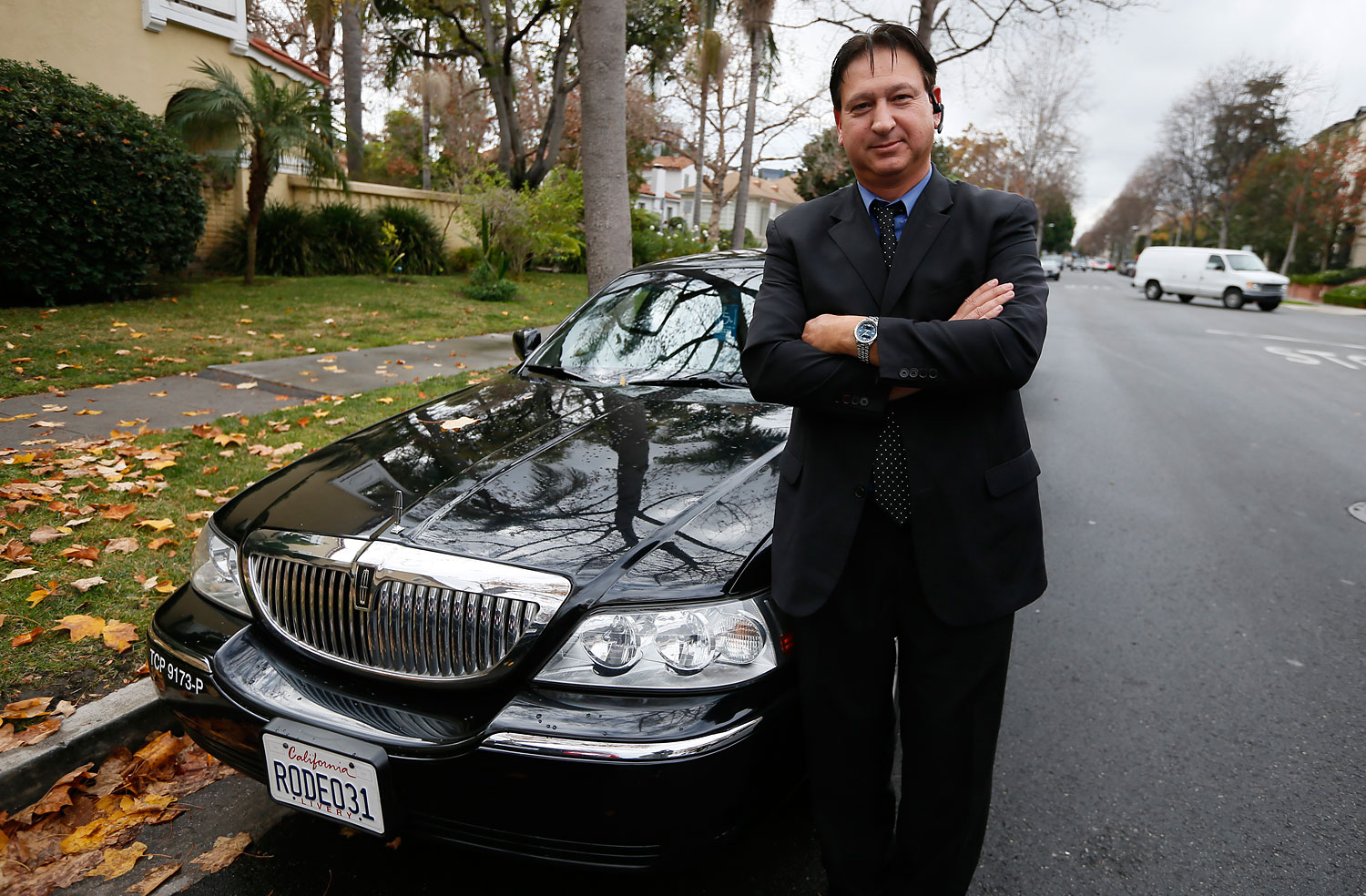 Uber driver Shuki Zanna poses in front of his limousine in Beverly Hills, California, in 2013.