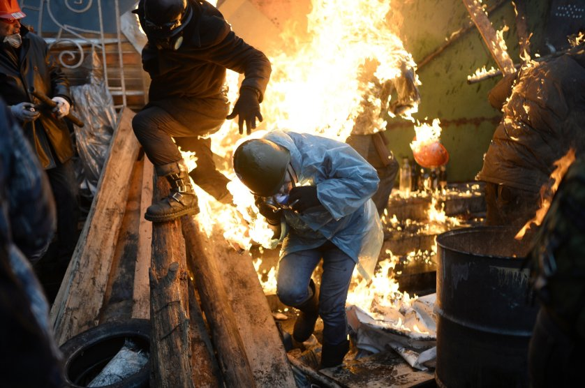 Protesters try to protect themselves from fire as they stand behind burning barricades during clashes with police on February 20, 2014 in Kiev.