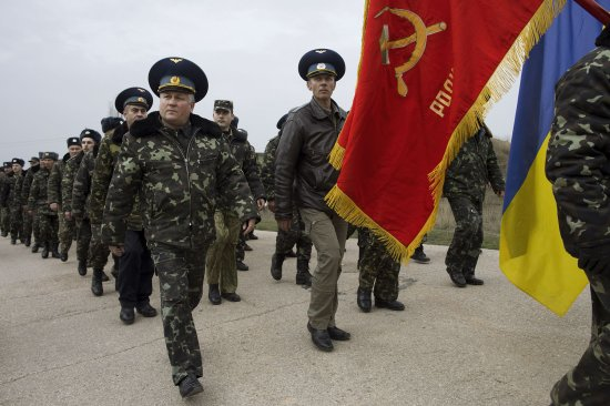Unarmed Ukrainian soldiers, carrying a Soviet air-regiment banner, approach Russian positions on the perimeter of the contested Belbek air-force base in Crimea, Ukraine, on March 4, 2014.