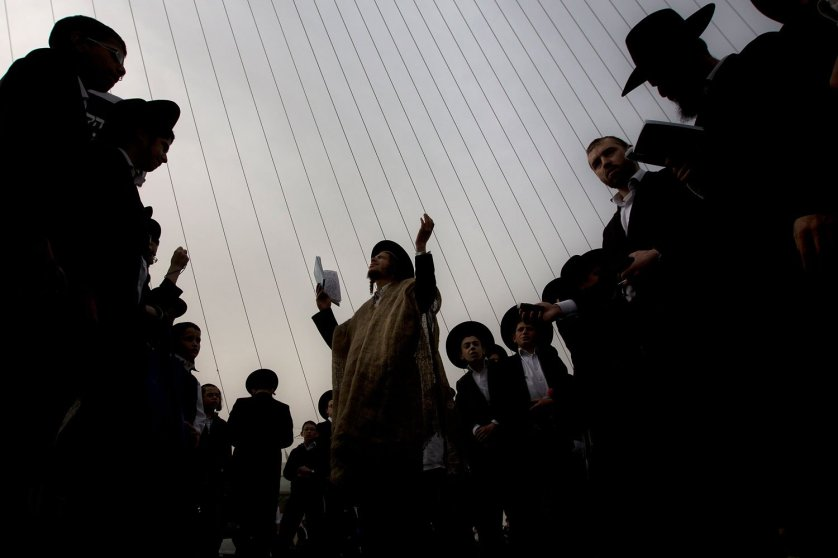Ultra-Orthodox Jewish men pray during a rally attended by hundreds of thousands against plans to force them to serve in the Israeli military, blocking roads and paralyzing the city of Jerusalem, March 2, 2014.