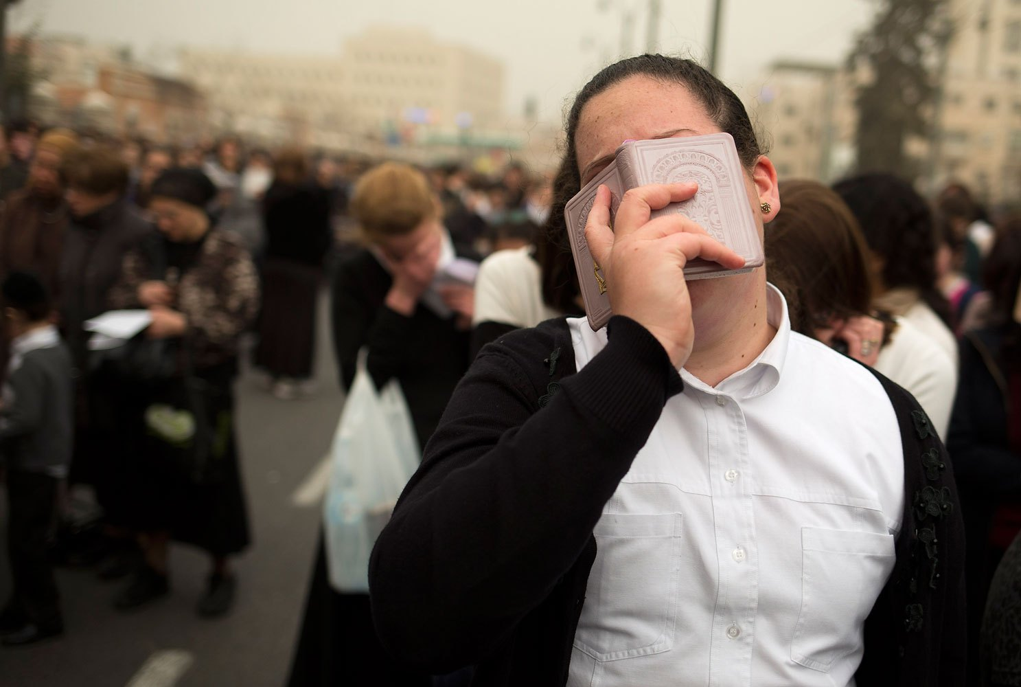 An ultra-Orthodox woman prays during a mass protest in Jerusalem, March 2, 2014.