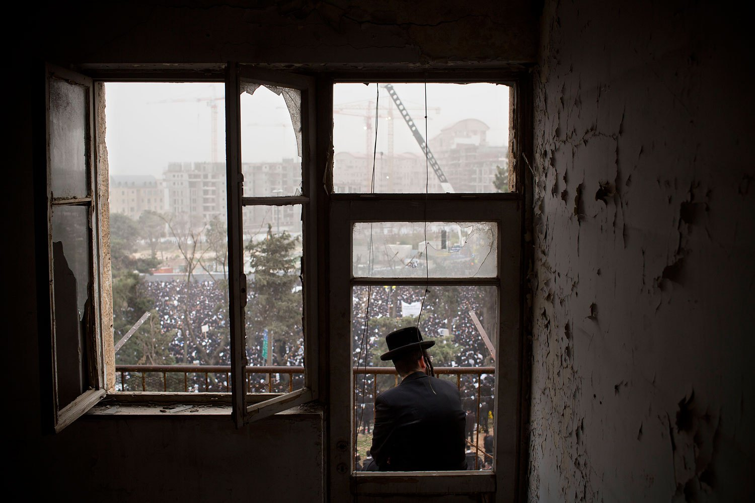 An ultra-Orthodox Jewish man watches from a balcony as hundreds of thousands of ultra-Orthodox Jews rally in a massive show of force against plans to force them to serve in the Israeli military, blocking roads and paralyzing the city of Jerusalem, March 2, 2014.