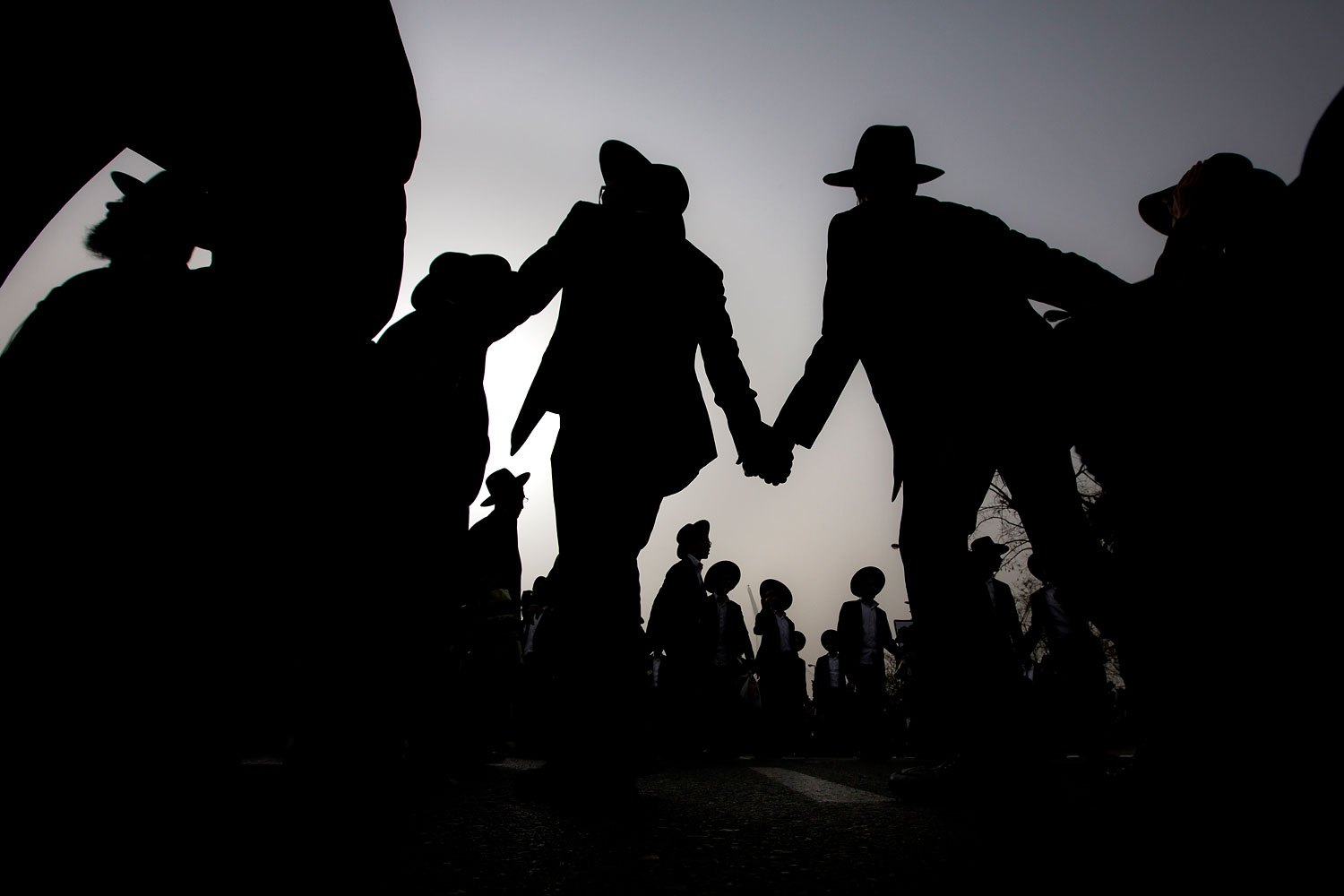 Ultra-Orthodox Jewish men dance at a rally in a massive show of force against plans to force them to serve in the Israeli military, blocking roads and paralyzing the city of Jerusalem, March 2, 2014.