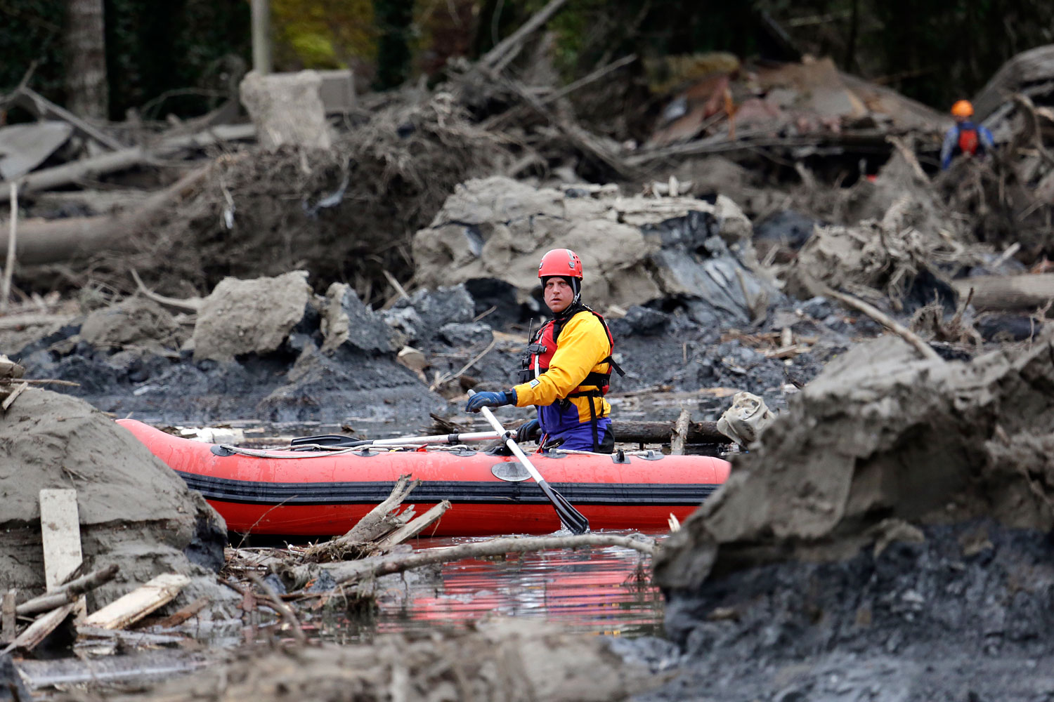 A searcher uses a small boat to look through debris from a deadly mudslide, March 25, 2014, in Oso, Wash.