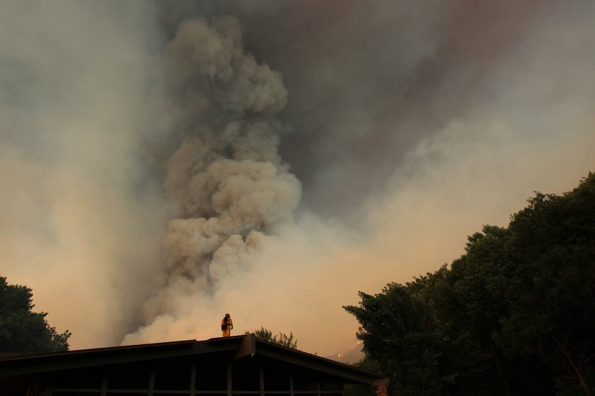 A firefighter watches from a rooftop as the Powerhouse fire closes in around the Canyon Creek Complex sports camp during a fast run toward Lake Hughes on June 1, 2013 south of Lake Hughes, Calif. The 19,500-acre wildfire destroyed numerous homes overnight.