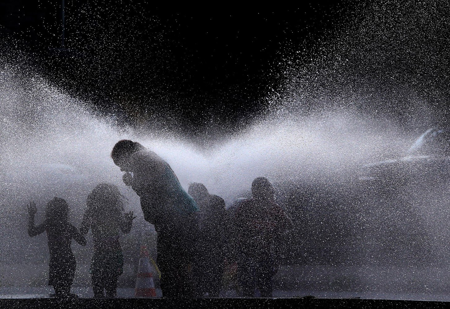 People cool off in the spray of an open hydrant on a hot evening in Lawrence, Mass., July 16, 2013. Americans across the northeast and midwest tried to keep their cool after several consecutive 90-degree days.