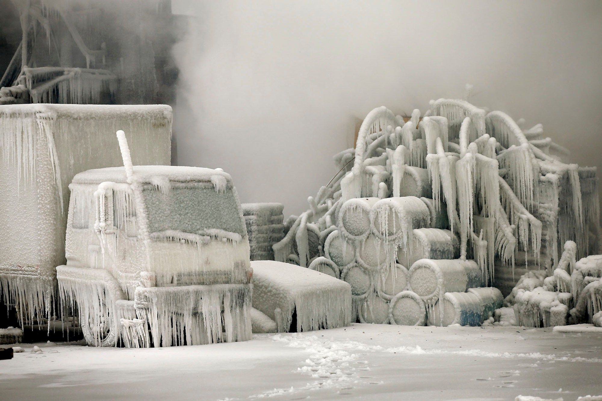 A truck is covered in ice as firefighters help to extinguish a massive blaze at a vacant warehouse on January 23, 2013 in Chicago. More than 200 firefighters battled a five-alarm fire as temperatures were in the single digits.