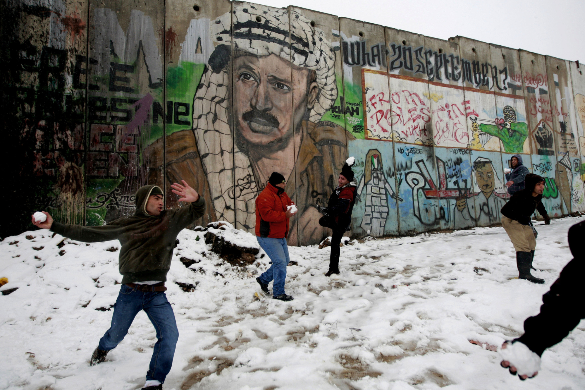 Palestinians play in the snow next to a section of Israel's separation barrier in Qalandia between Jerusalem and the West bank city of Ramallah, Jan. 10, 2013. The storm was the biggest of its kind to hit the region in 30 years.