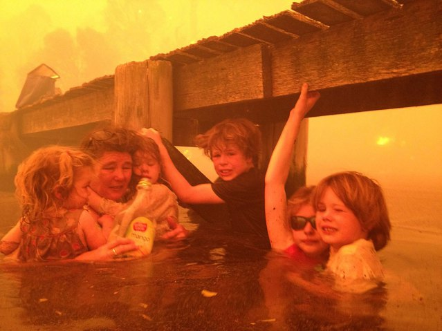 Tammy Holmes, second left, takes shelter with her grandchildren, from left, Charlotte Walker, 2, Esther Walker, 4, Liam Walker, 9, Matilda, 11, and Caleb Walker, 6, under a jetty as a wildfire rages nearby in Dunalley, Australia, Jan. 4, 2013.