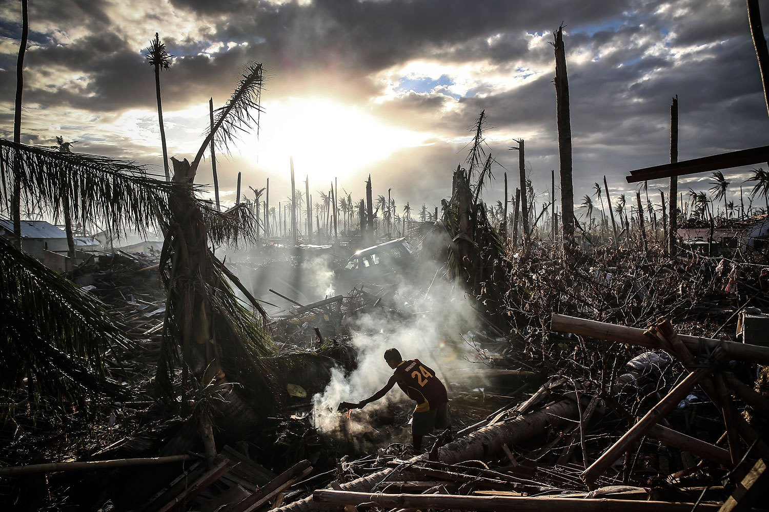 A man fans flames on a fire in Tanauan, Leyte province, Philippines, on November 19, 2013. Typhoon Haiyan devastated the nation leaving at least 6,000 dead.