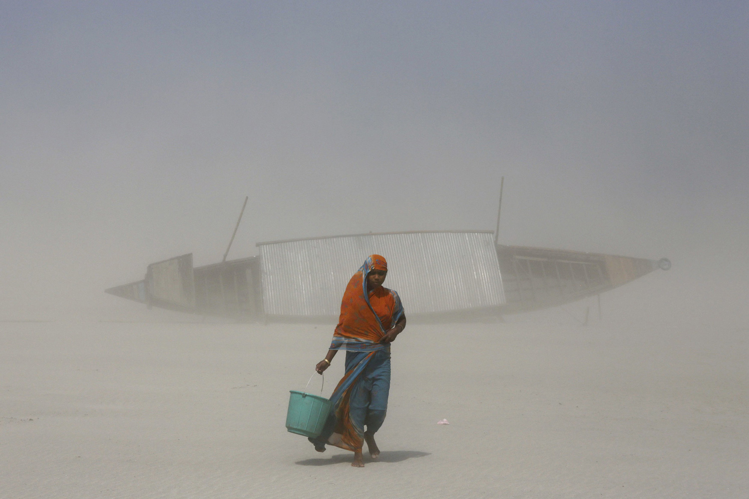 An Indian woman carries a bucket filled with drinking water as she walks on dry mud against blowing sand, along the Brahmaputra river in Gauhati, India, March 21, 2014.