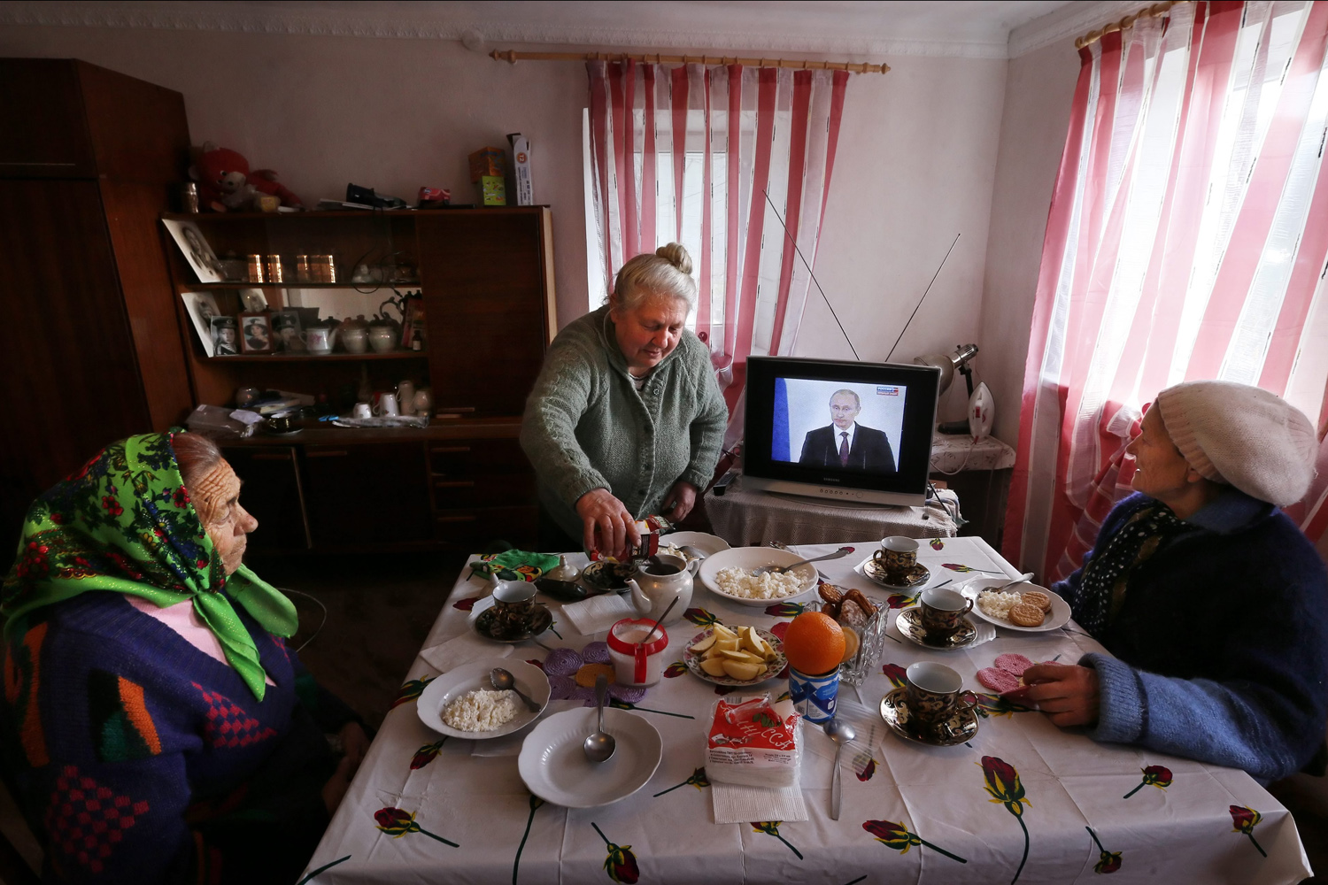 Mar. 18,  2014. Women have their lunch as they watch Russian President Vladimir Putin on the television addressing the Russian Federal Assembly on the Crimean referendum to reunify with Russia outside Simferopol, Crimea, Ukraine.