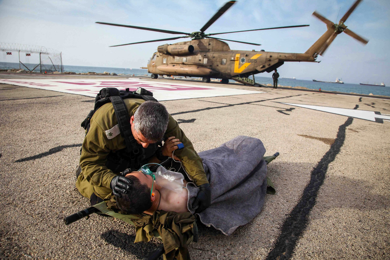 Mar. 18, 2014. An Israeli army officer comforts a wounded Israeli soldier after he is unloaded from an army helicopter at a landing base in Haifa's Rambam Hospital, in northern Israel.