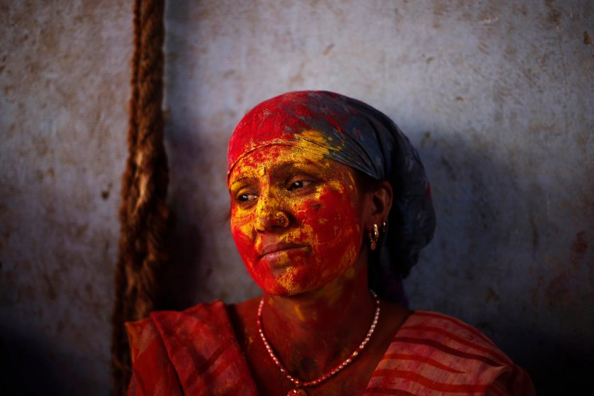 """A Hindu woman is seen covered with coloured powder at a temple during """"Lathmar Holi"""" at Nandgaon village"""