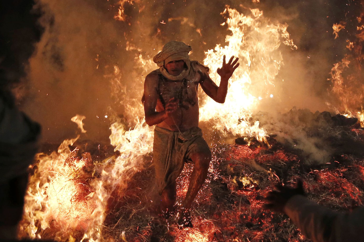 Mar. 17, 2014. Hindu priest Babulal jumps out of a fire to signify the burning of the demon Holika during a ritual to mark the first day of the Holi spring festival, also known as the Festival of Colours, at village Phalen near the northern Indian city of Mathura.