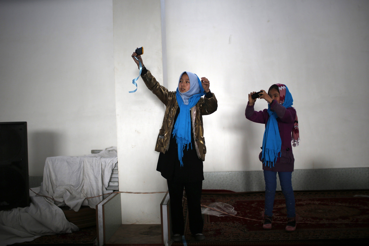 March 17, 2014. Afghan girls use their phones to take pictures during a campaign for Afghan presidential candidate Zalmai Rassoul in Kabul The Afghan presidential elections will be held on April 5.