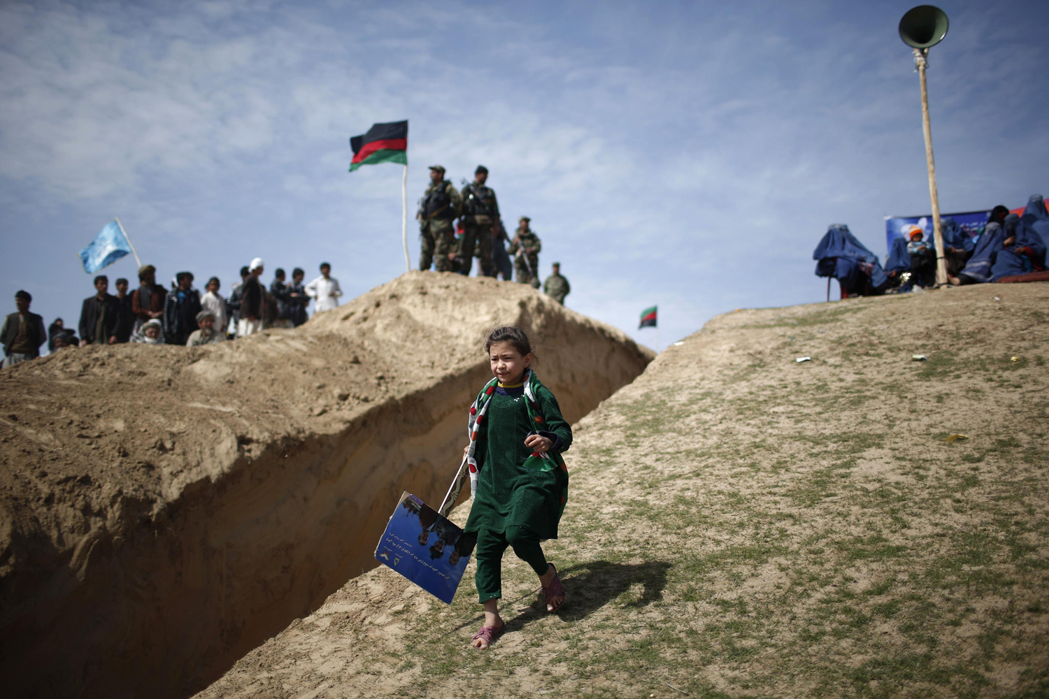 Mar. 19, 2014. A girl runs during an election campaign by Afghan presidential candidate Ashraf Ghani Ahmadzai in Kunduz province, northern Afghanistan  The Afghan presidential elections will be held on April 5.