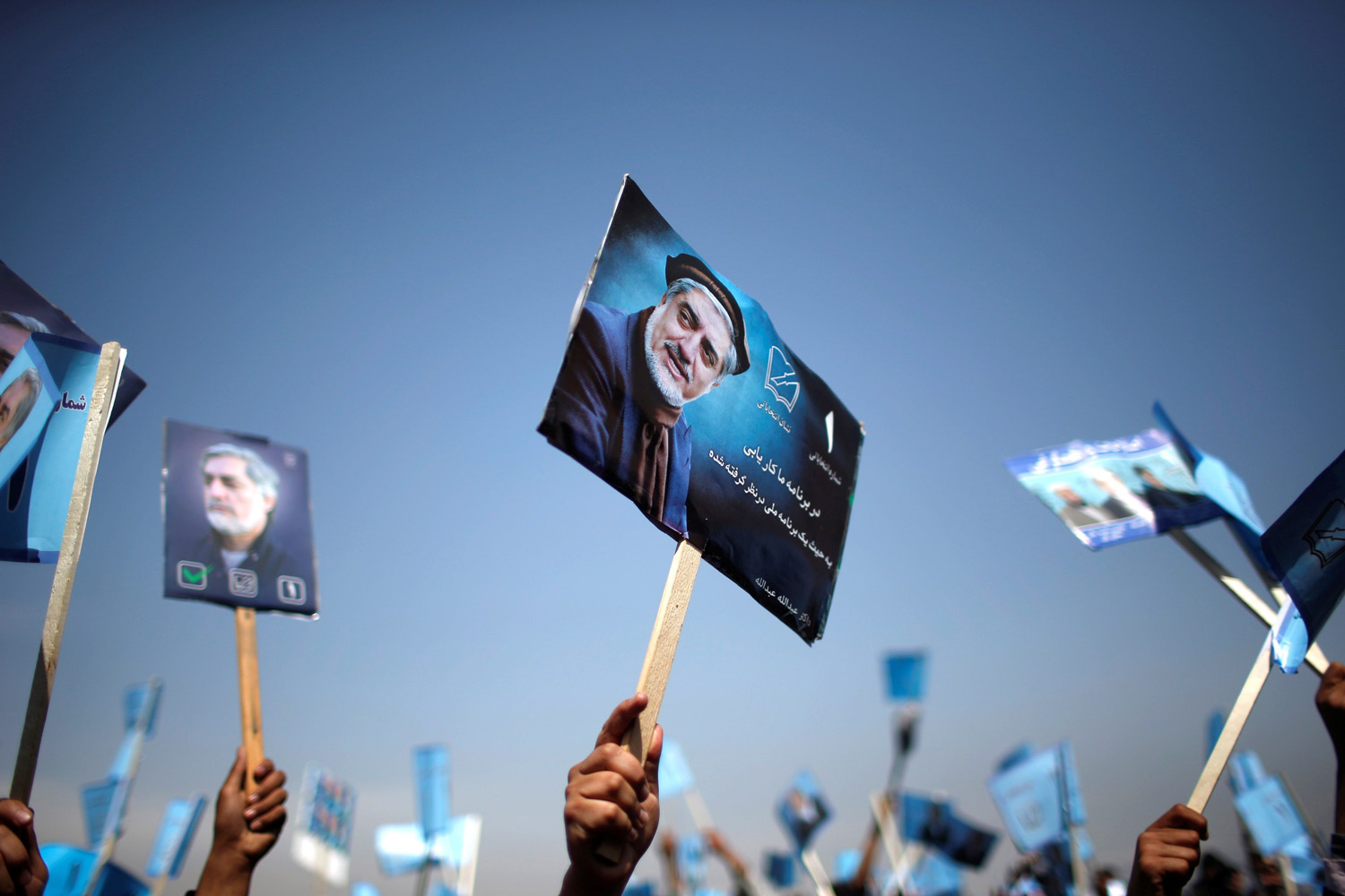 Mar. 20, 2014. Supporters of Afghan presidential candidate Abdullah Abdullah hold posters of him during an election rally in Parwan province, northern Afghanistan.