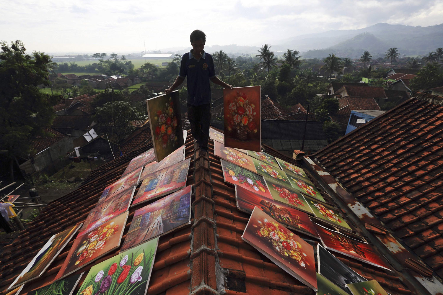 Mar. 20, 2014. An artist walks across the roof of his house while carrying paintings to be dried at Jelekong village near Bandung, in Indonesia's West Java province. The people of Jelekong village earn their living by selling their paintings.