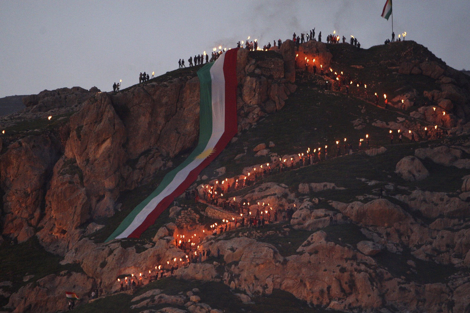 Mar. 20, 2014. Iraqi Kurdish people carry fire torches up a mountain where a giant flag of Iraq's autonomous Kurdistan region is laid, as they celebrate Newroz Day, a festival marking their spring and new year, near Dahuk, Iraq.