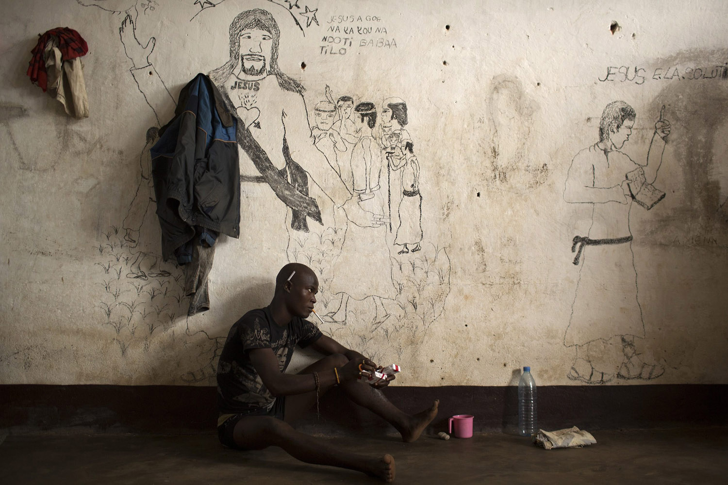 Mar. 21, 2014. A man sits next to a wall with graffiti in a cell of the central prison in the district of Wango, in the capital Bangui, Central African Republic.