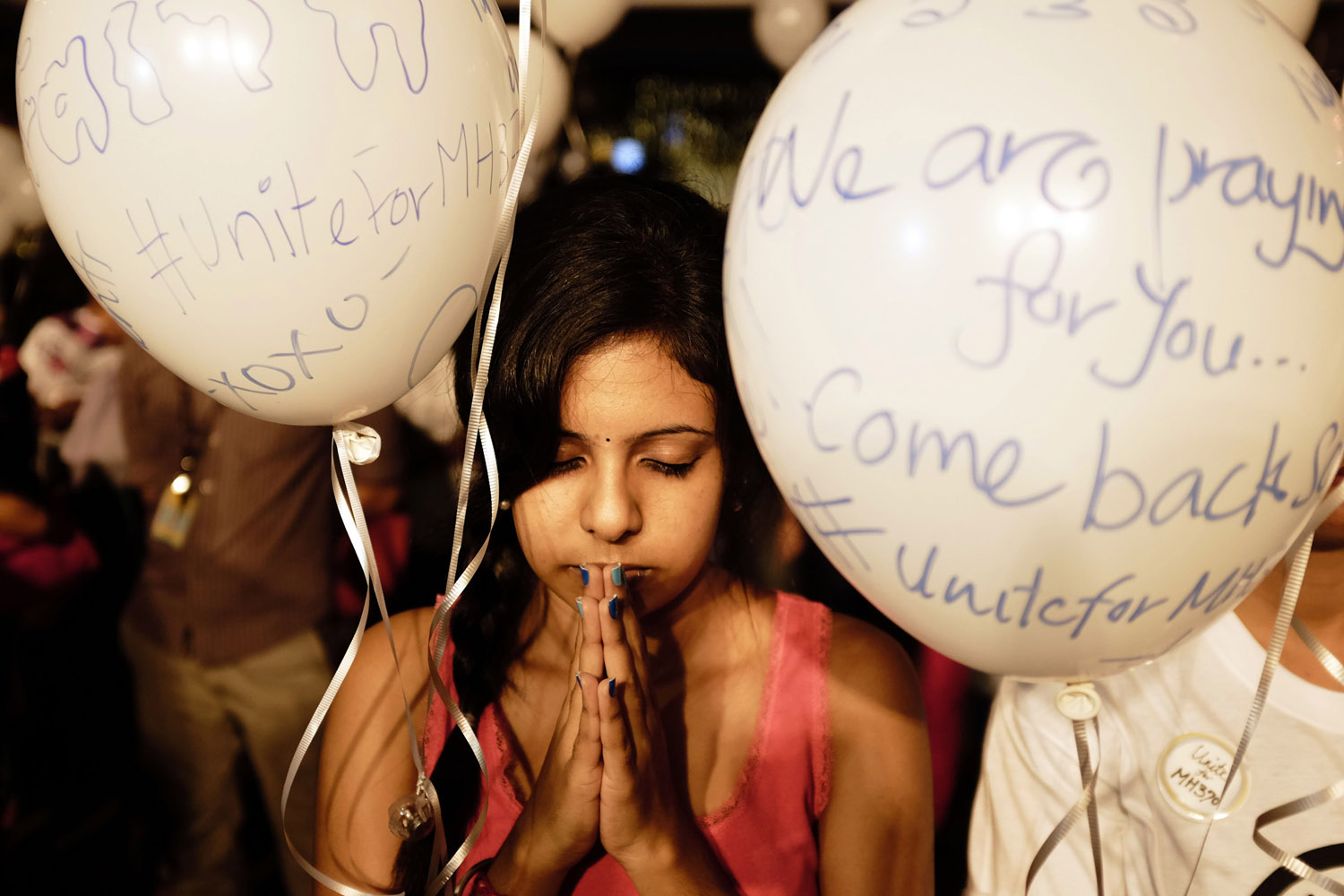 Mar. 18, 2014 - A girl prays during an event for missing Malaysia Airlines Flight MH370 at a shopping mall in Petaling Jaya,  Malaysia  A coalition of 26 countries, including Thailand, are looking for the flight, which vanished with 239 people aboard.