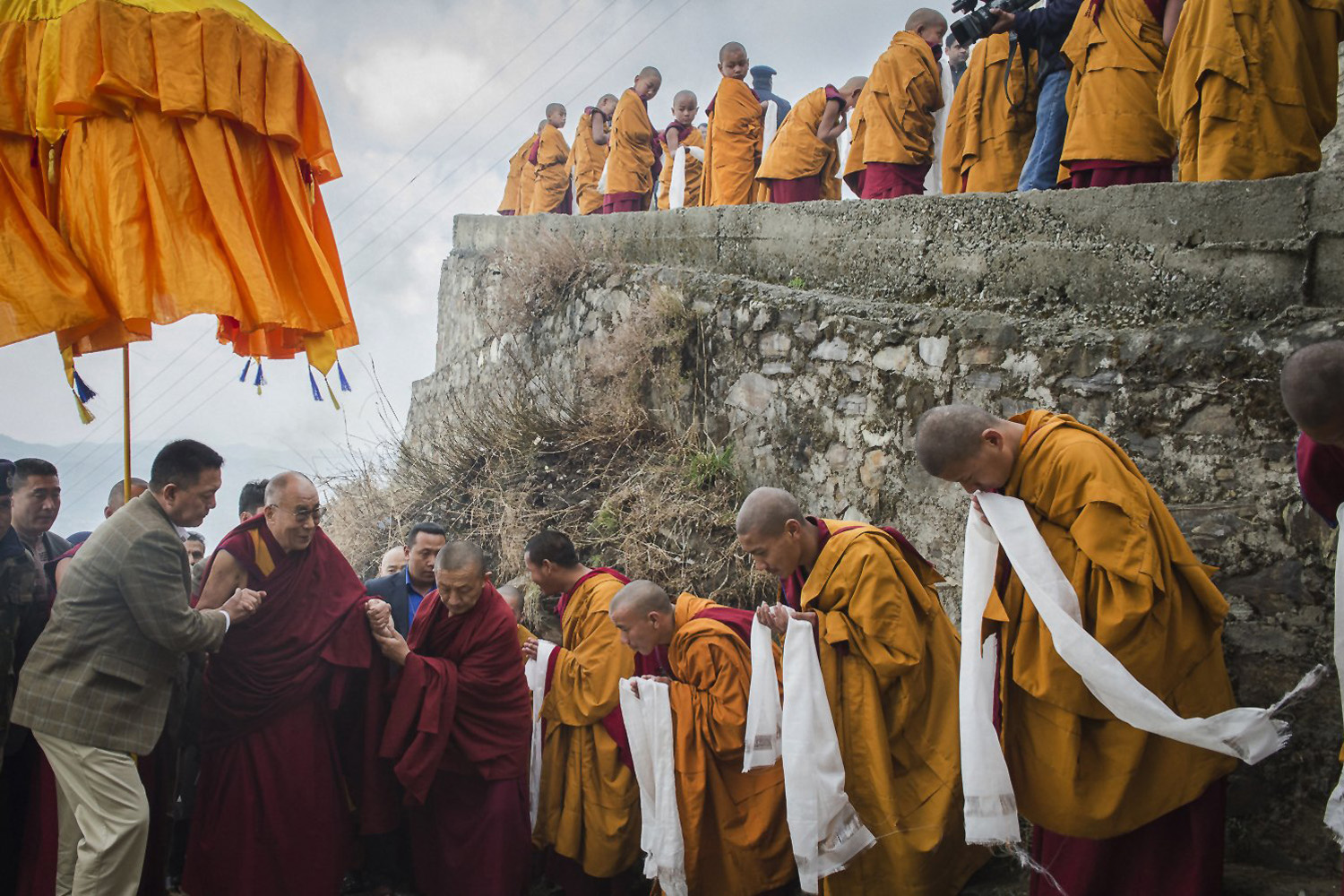 Mar. 18, 2014. Tibetan Buddhist monks holding ceremonial scarfs stand in a line to welcome their spiritual leader the Dalai Lama, fourth left, as he arrives at the Jhonang Takten Phuntsok Choeling monastery in Shimla, India.